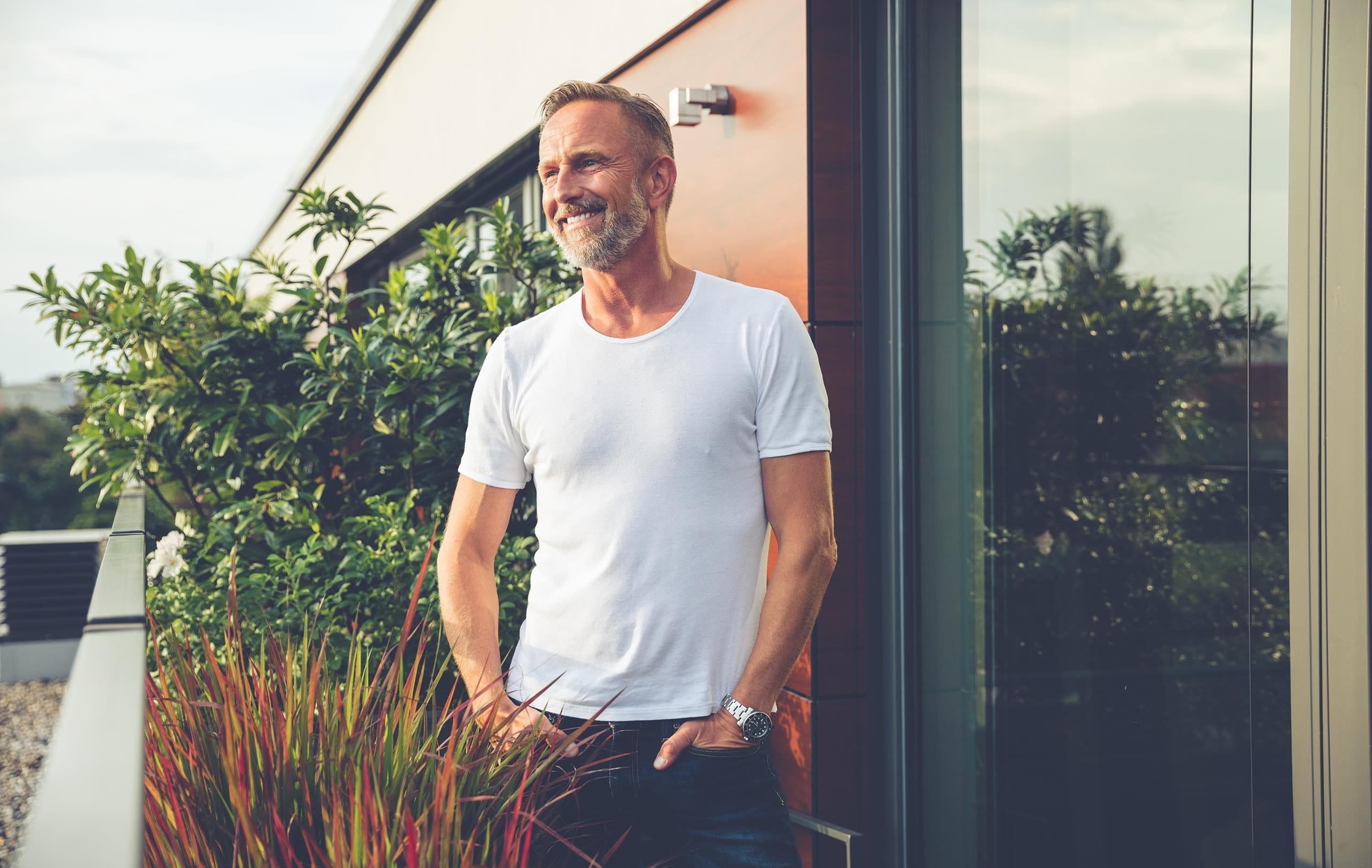 Mann in weissem T-shirt steht lächelnd auf dem Balkon