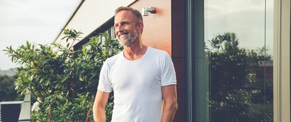 Uomo in T-shirt bianco sorridente sul balcone