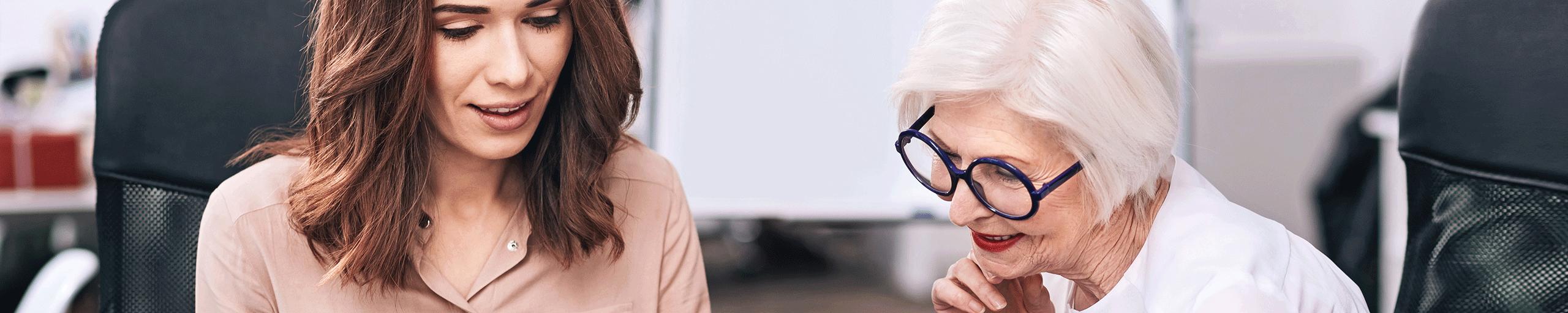 Eine jüngere und ältere Geschäftsfrau besprechen das Projekt