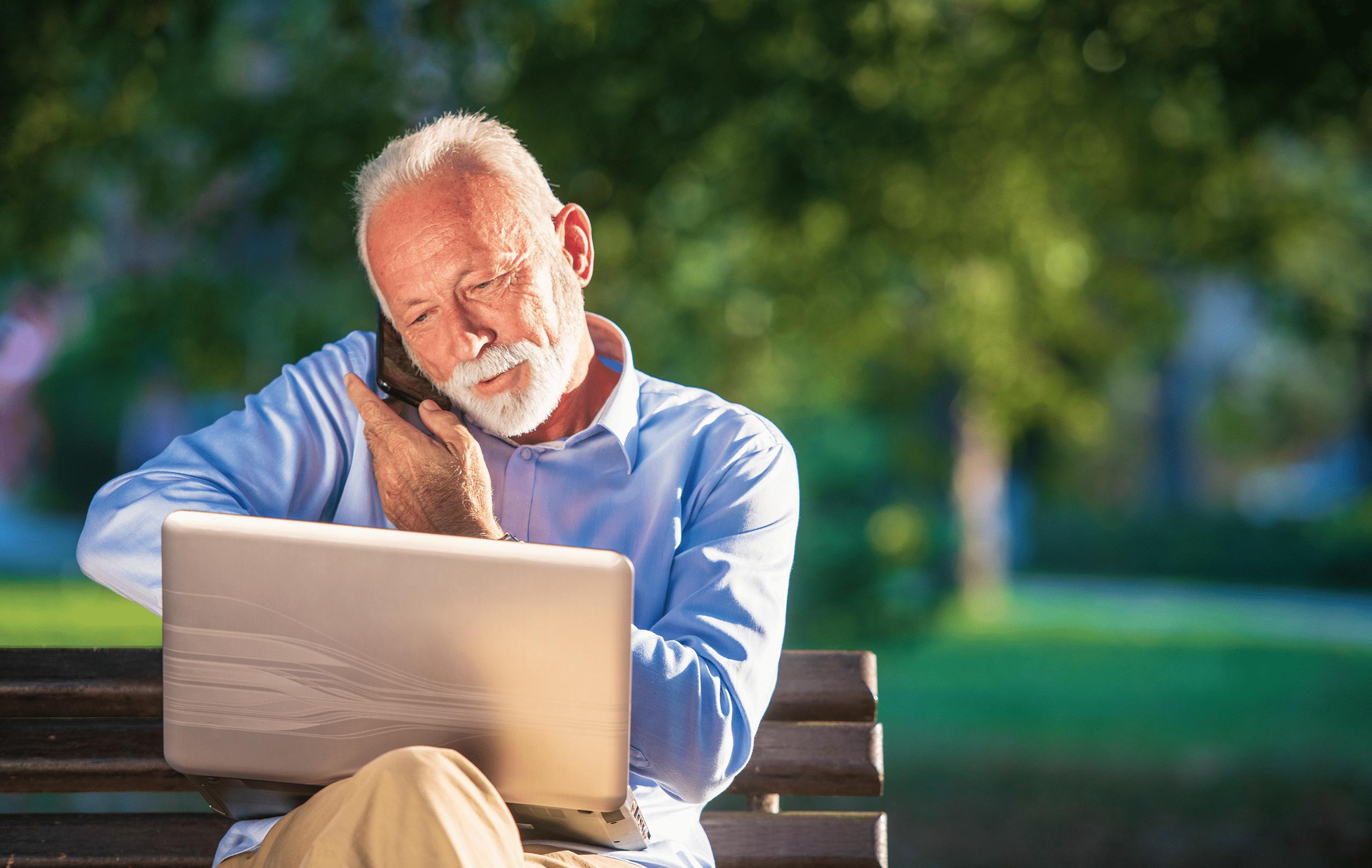 Älterer Herr sitzt auf Parkbank, telefoniert und hat Laptop auf den Knien
