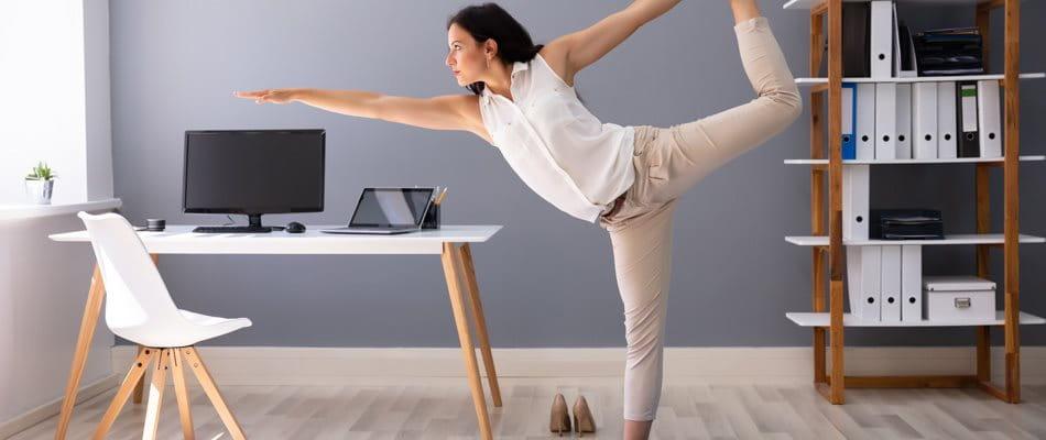 Une femme fait du yoga au bureau à domicile