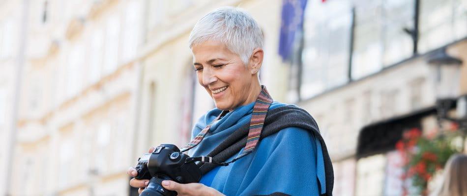 Femme dans une ville souriant à son appareil photo
