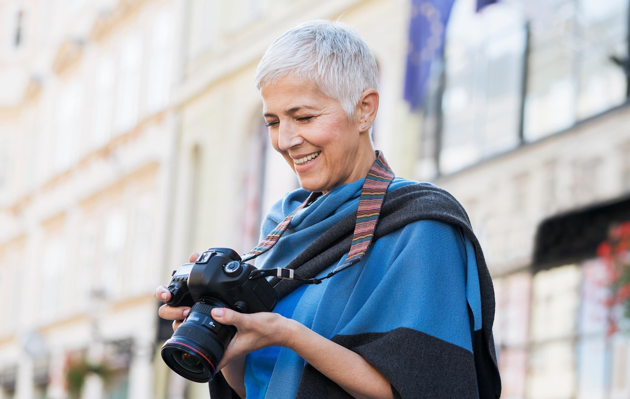 Frau steht in einer Stadt und schaut lächelnd auf ihre Kamera
