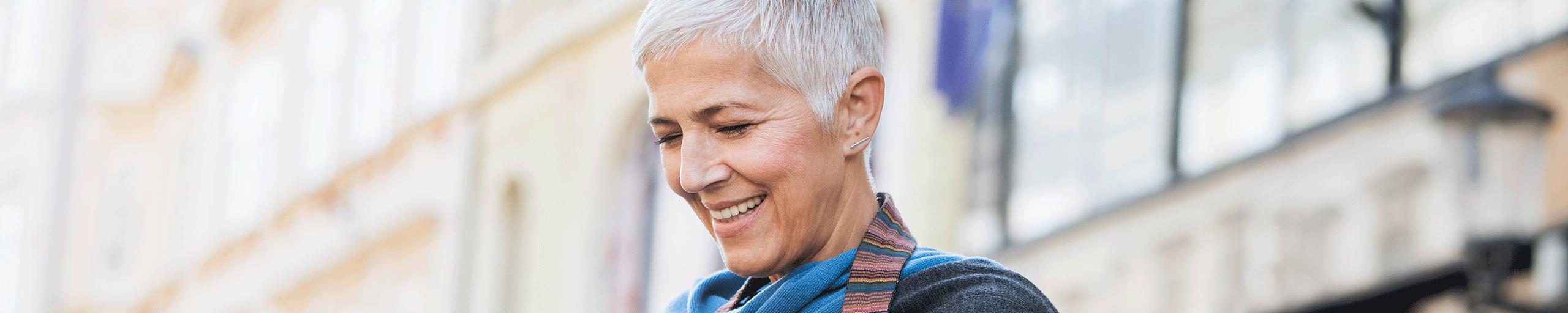 Donna che si è trovata in una città a sorridere alla sua macchina fotografica
