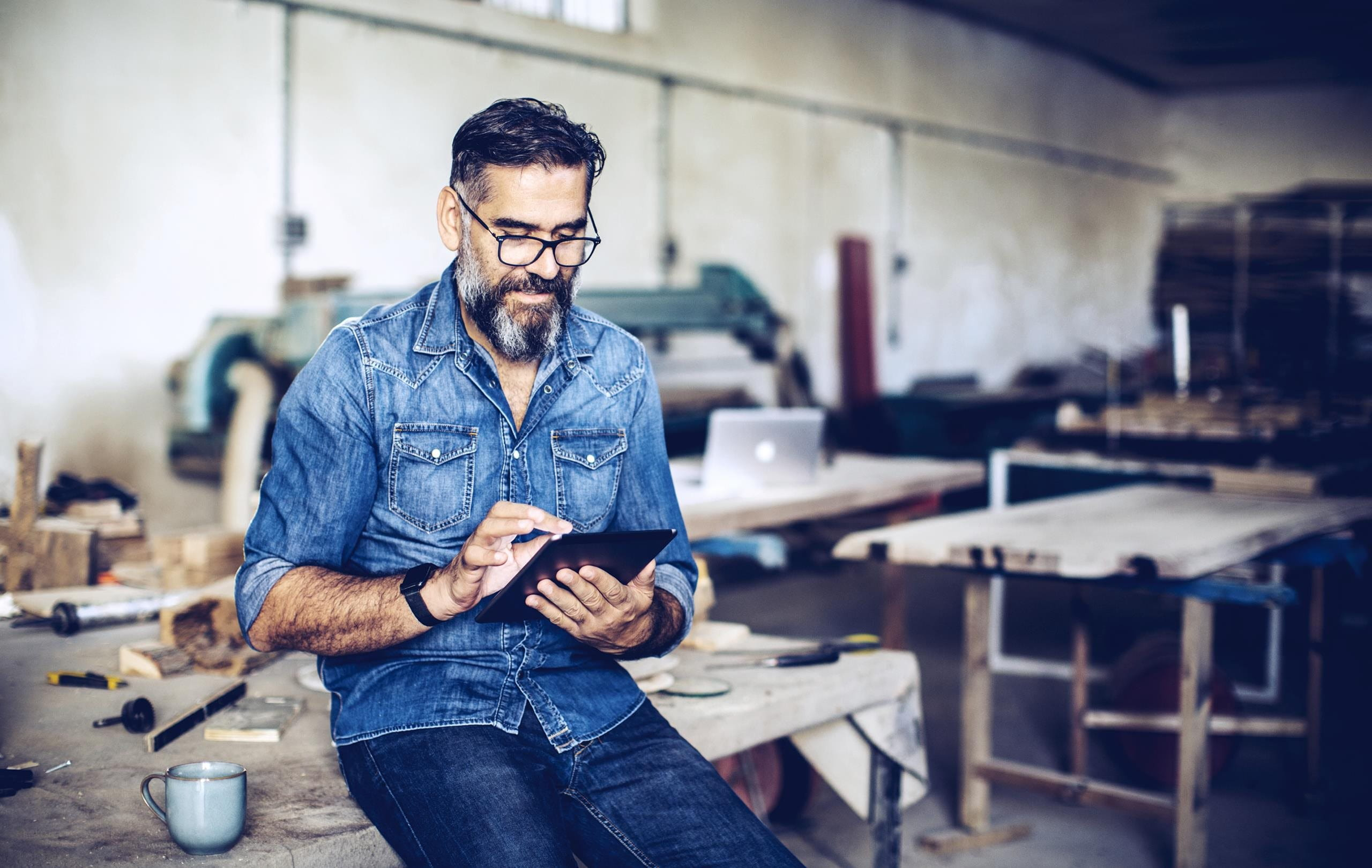 Mann sitzt auf Werkbank und schaut ins iPad