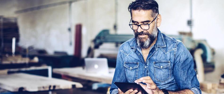 Mann sitzt in seiner Werkstatt und analysiert auf seinem Tablet verschiedene Pensionskassenlösungen