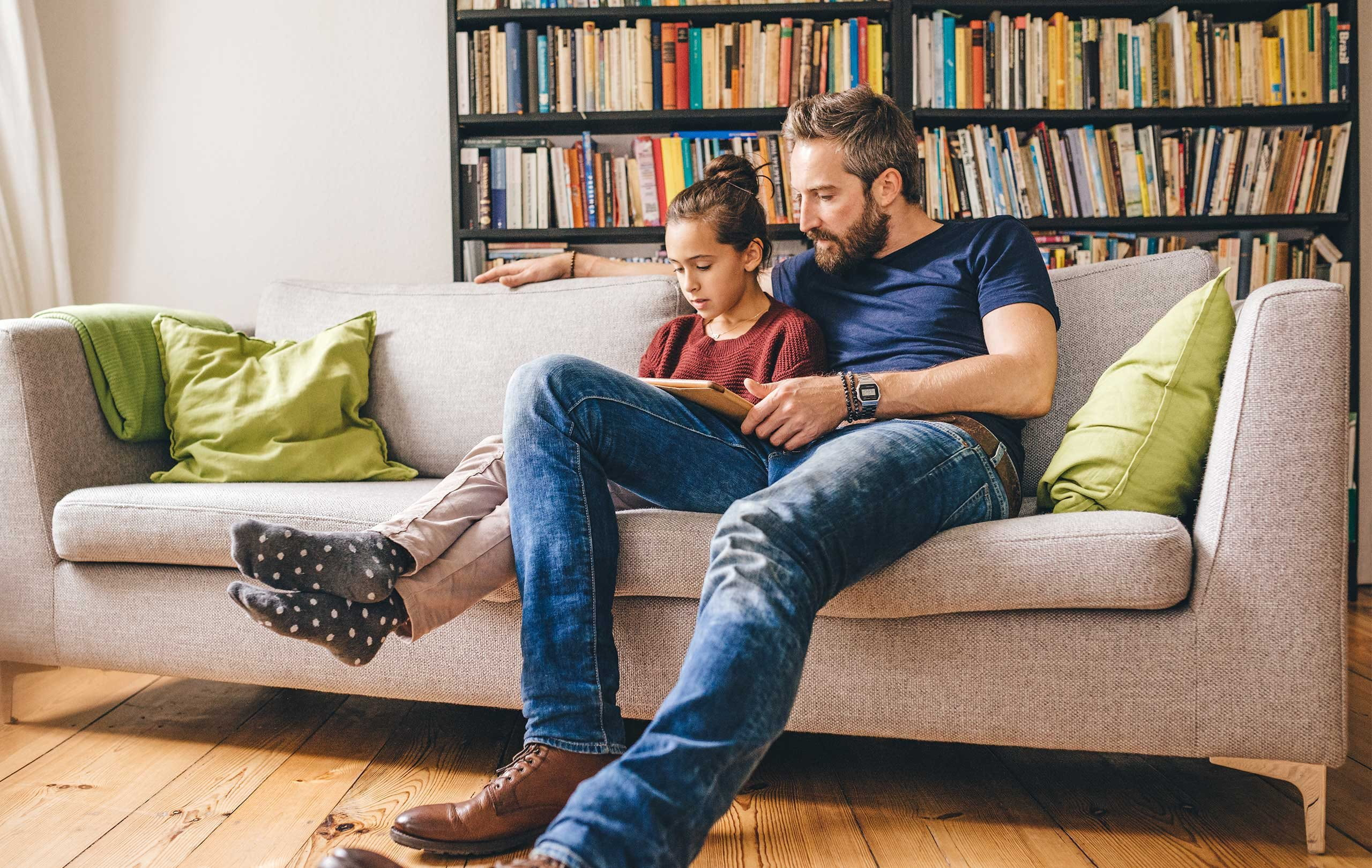 Father sits with daughter on the sofa and reads a book