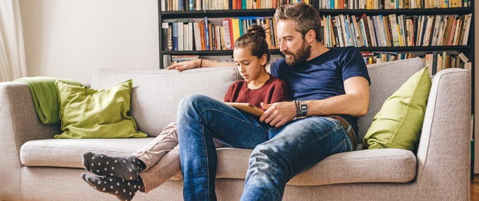 Vater sitzt mit Tochter auf dem Sofa und liest ein Buch