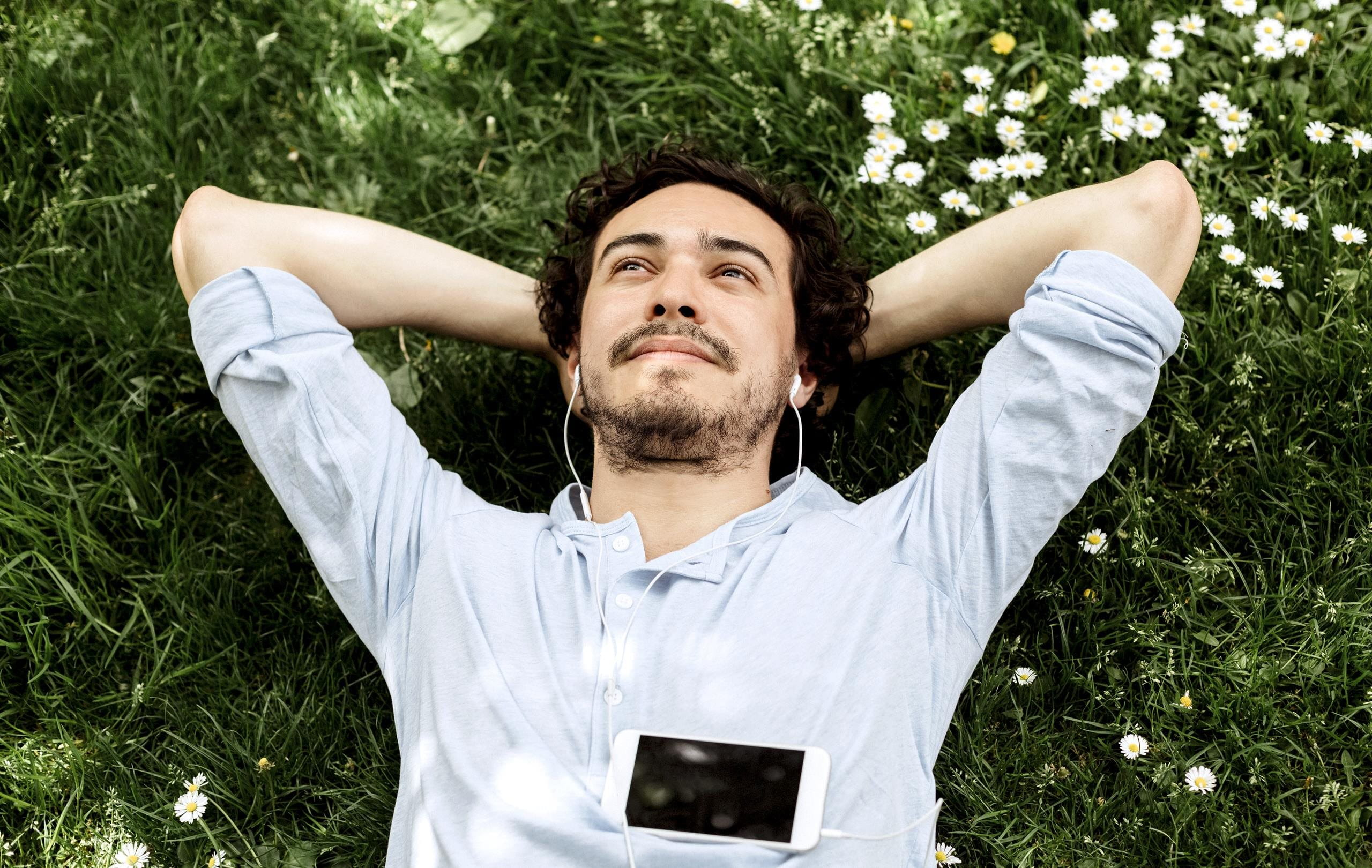 Man lies on meadow, looks into the sky and listens to music.