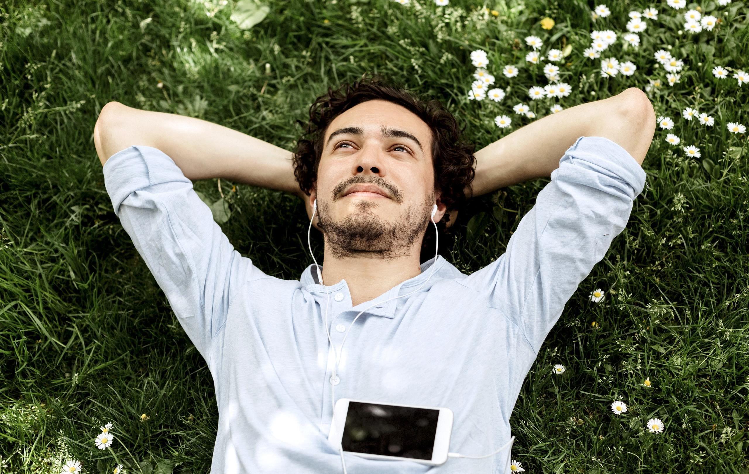 Mann liegt auf Wiese, schaut in den Himmel und hört Musik.