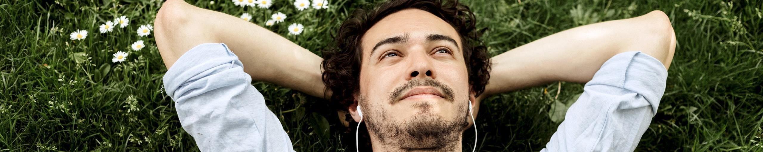 L'uomo giace sul prato, guarda il cielo e ascolta la musica.