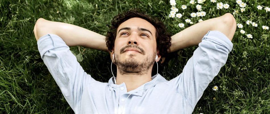 L'homme s'allonge sur la prairie, regarde le ciel et écoute de la musique.
