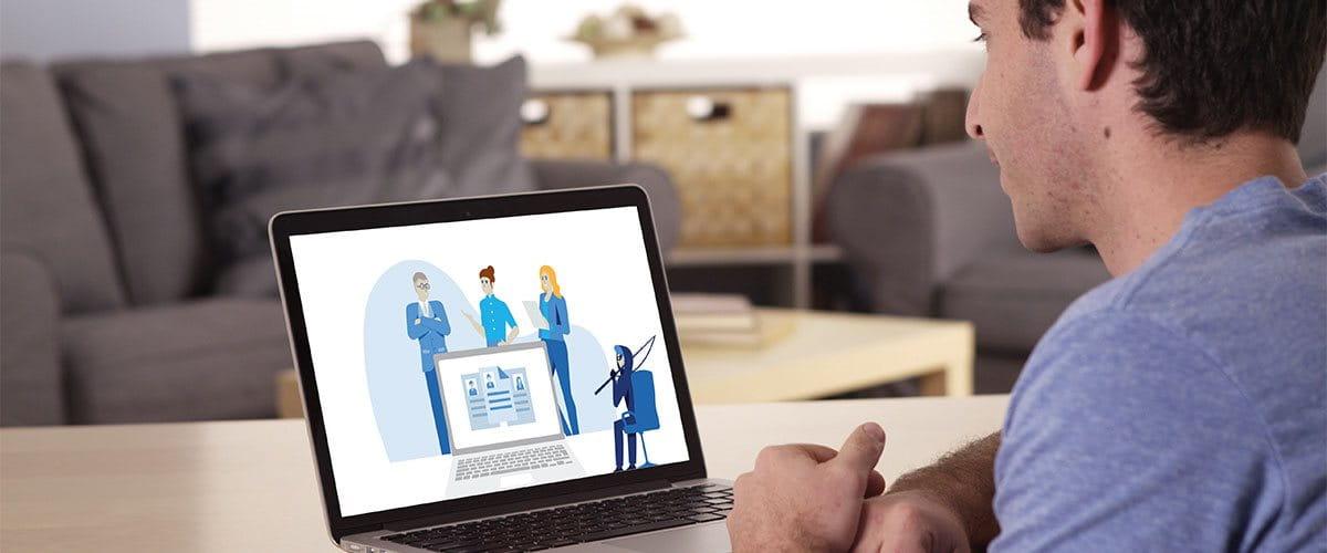 Ein Mann schaut sich auf einem Laptop das Cyberversicherungs-Video an.