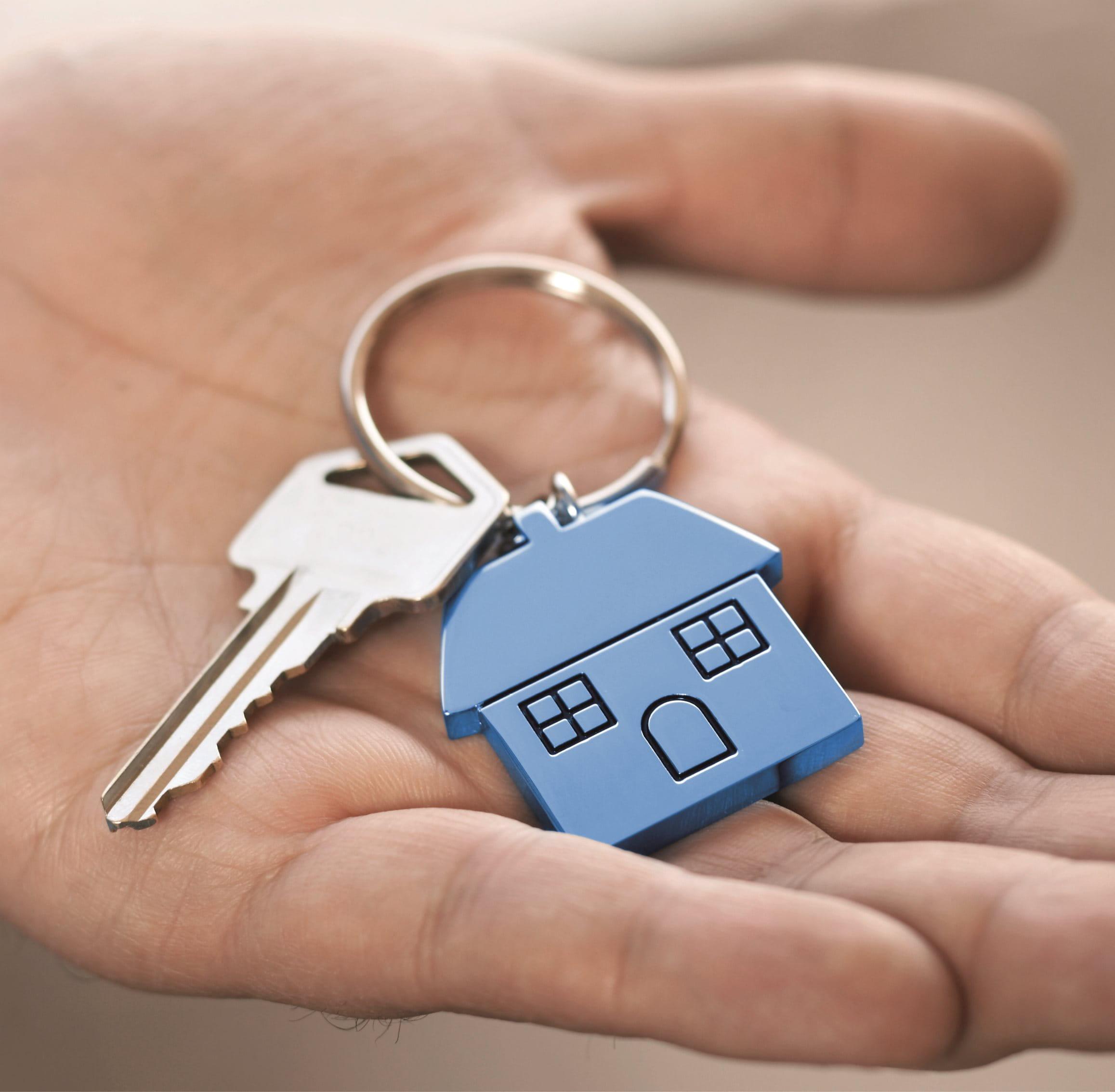 Main avec clé et porte-clés bleue dans la main