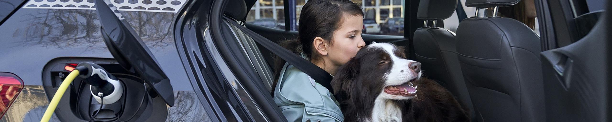 Maedchen kuschelt einen Hund im Auto