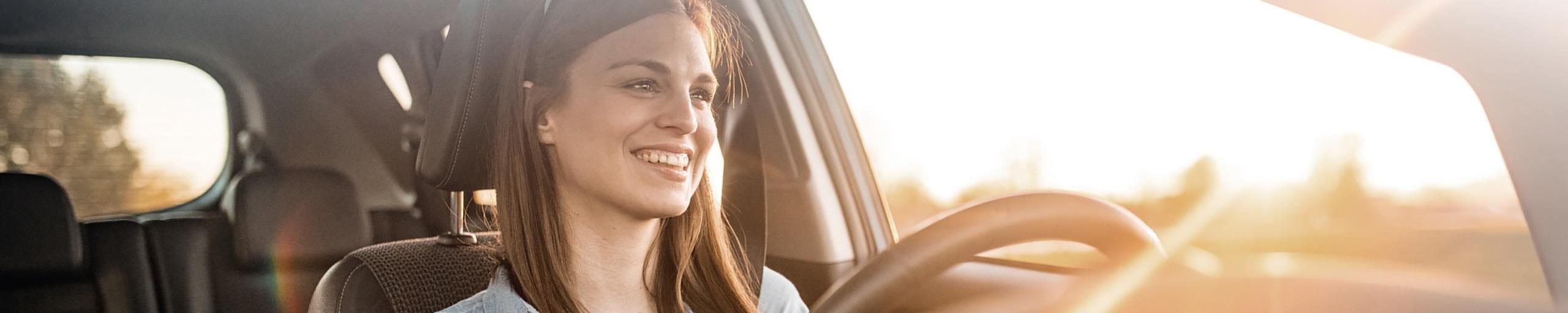 Giovane donna seduta al volante di una macchina