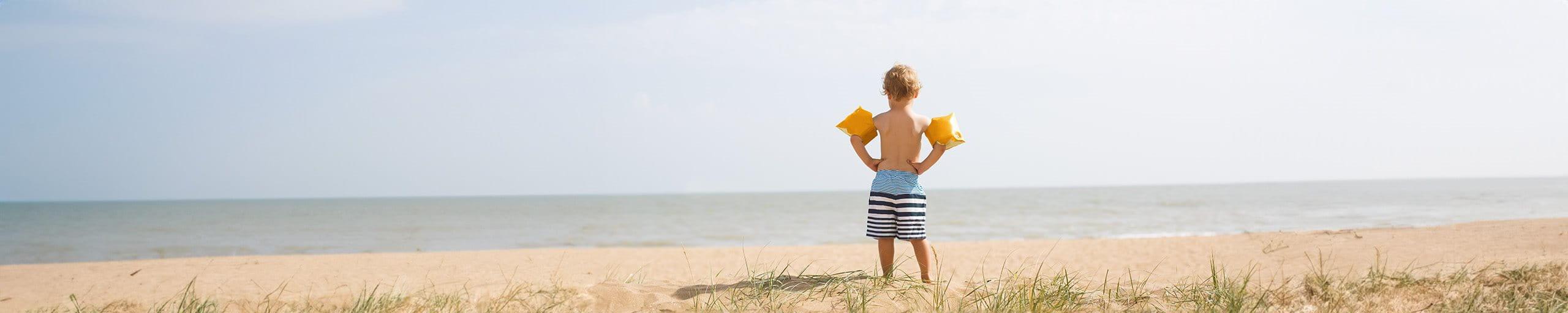 Ein Junge mit Schwimmflügeln planscht im Wasser.