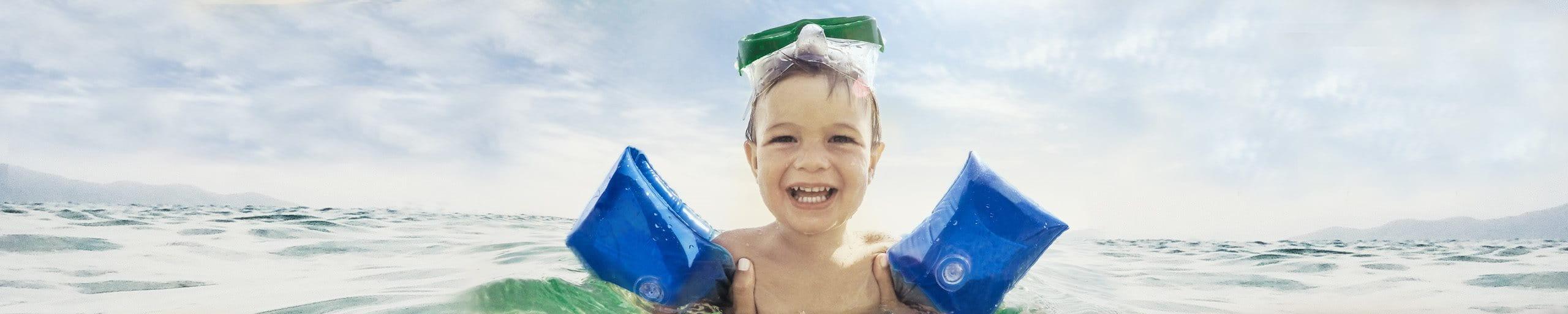 Un garçon avec des brassards patauge dans l'eau.