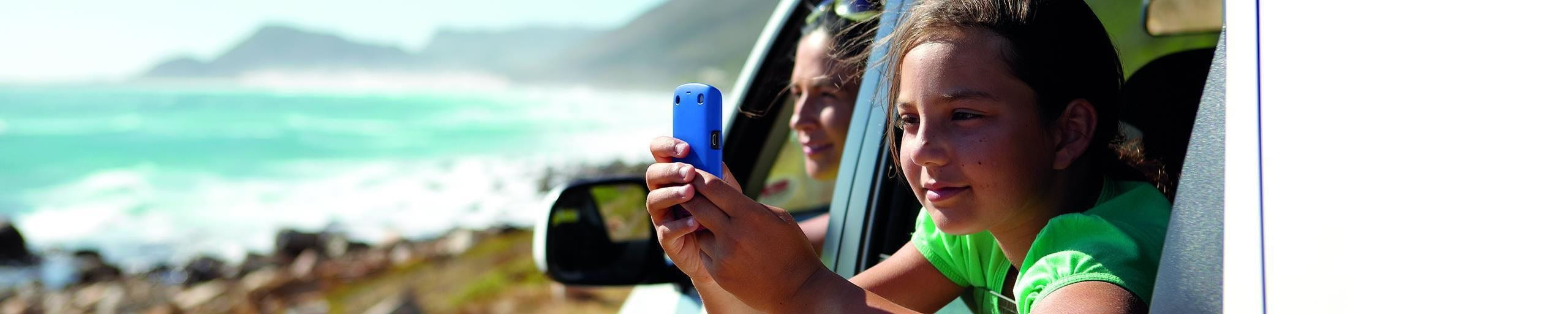 Child with cell phone in the car