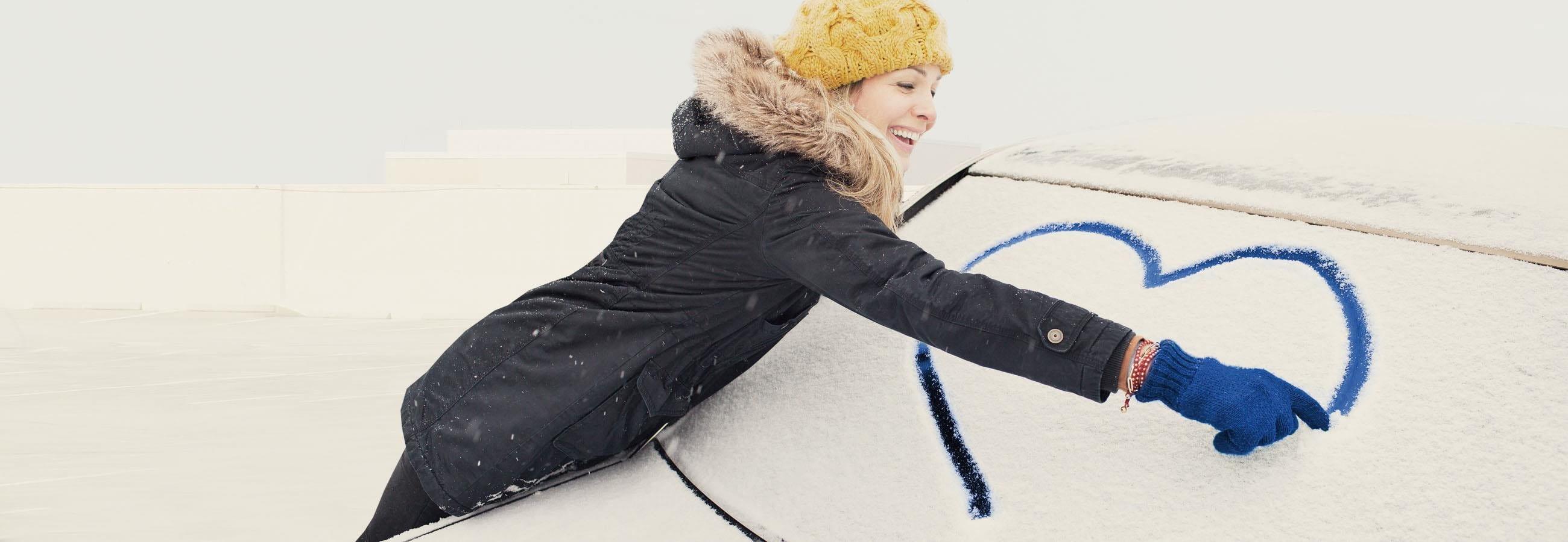 Frau malt Herz auf Autoscheibe
