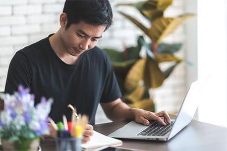 Ein junger Mann arbeitet auf einem Laptop und macht nebenbei Notizen.