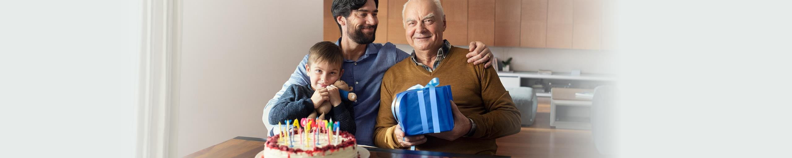 Father, son and grandson with birthday cake and present