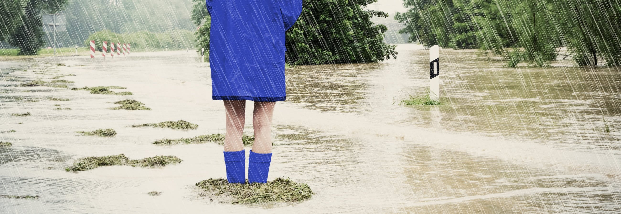 Woman standing in a flood wearing a raincoat and rubber boots