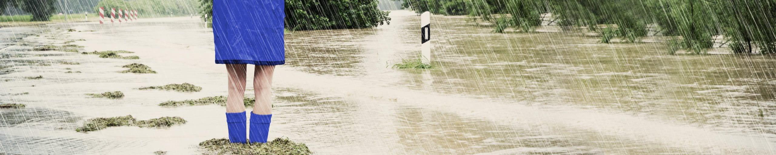 Frau steht mit Regenjacke und Gummistiefel im Hochwasser