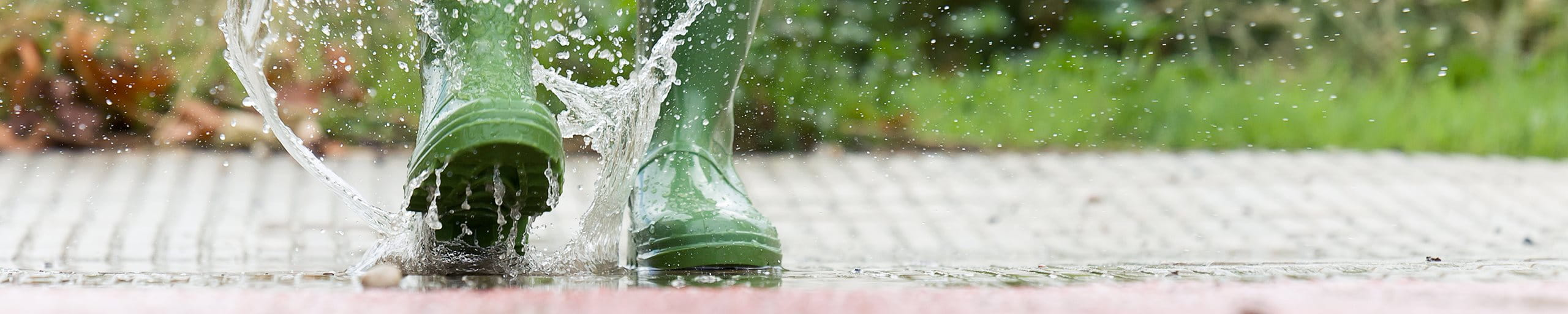 Woman jumps into puddle in green wellies