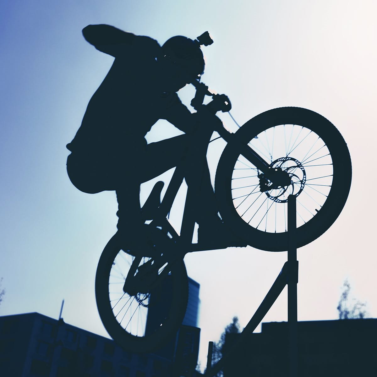 BMX rider with helmet camera against back light while jumping an obstacle