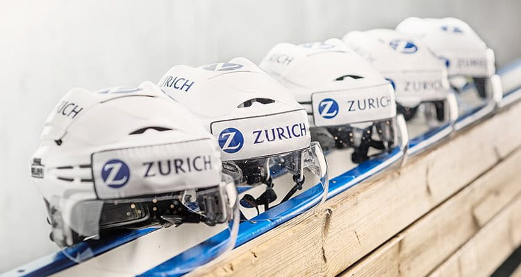 A row of ice hockey helmets featuring the Zurich logo