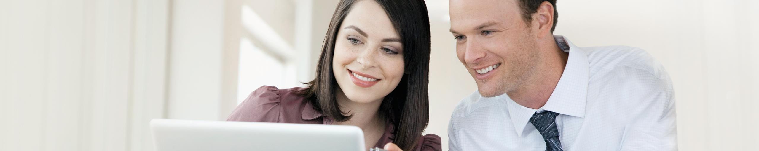 Zwei Personen schauen auf den Computer.