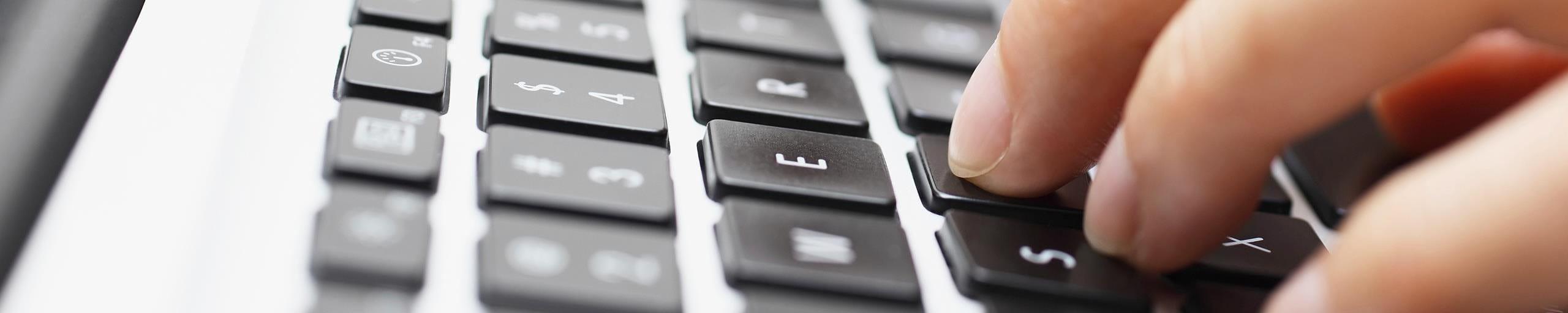 Une personne tape un texte sur son ordinateur.