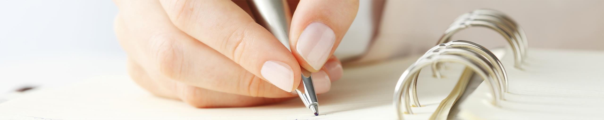 Une main de femme écrit quelque chose sur son agenda