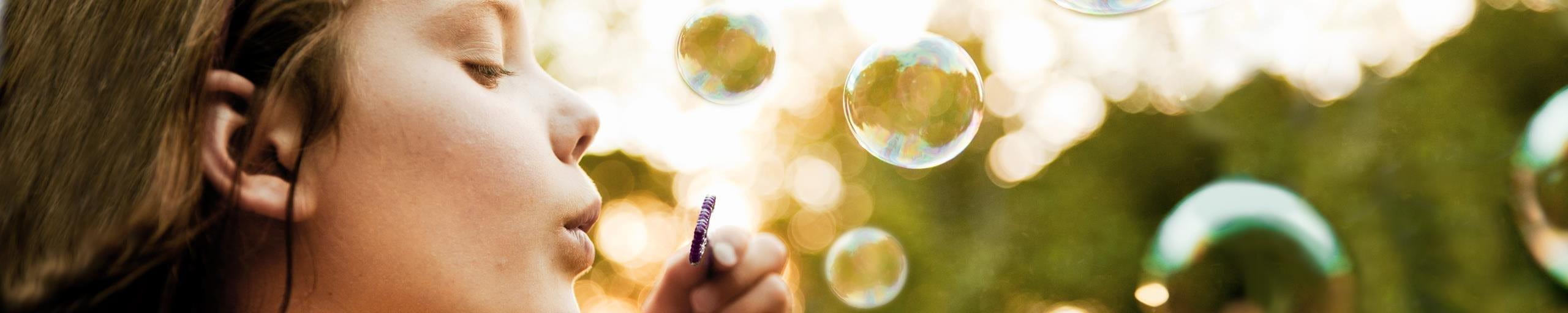 Ein Mädchen macht Seifenblasen.
