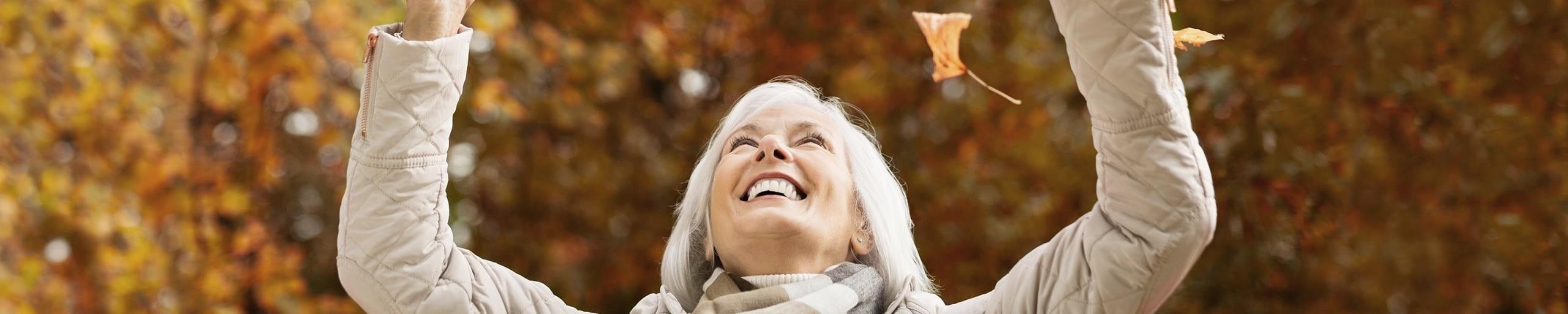 Una donna butta sorridendo delle foglie secche in aria.