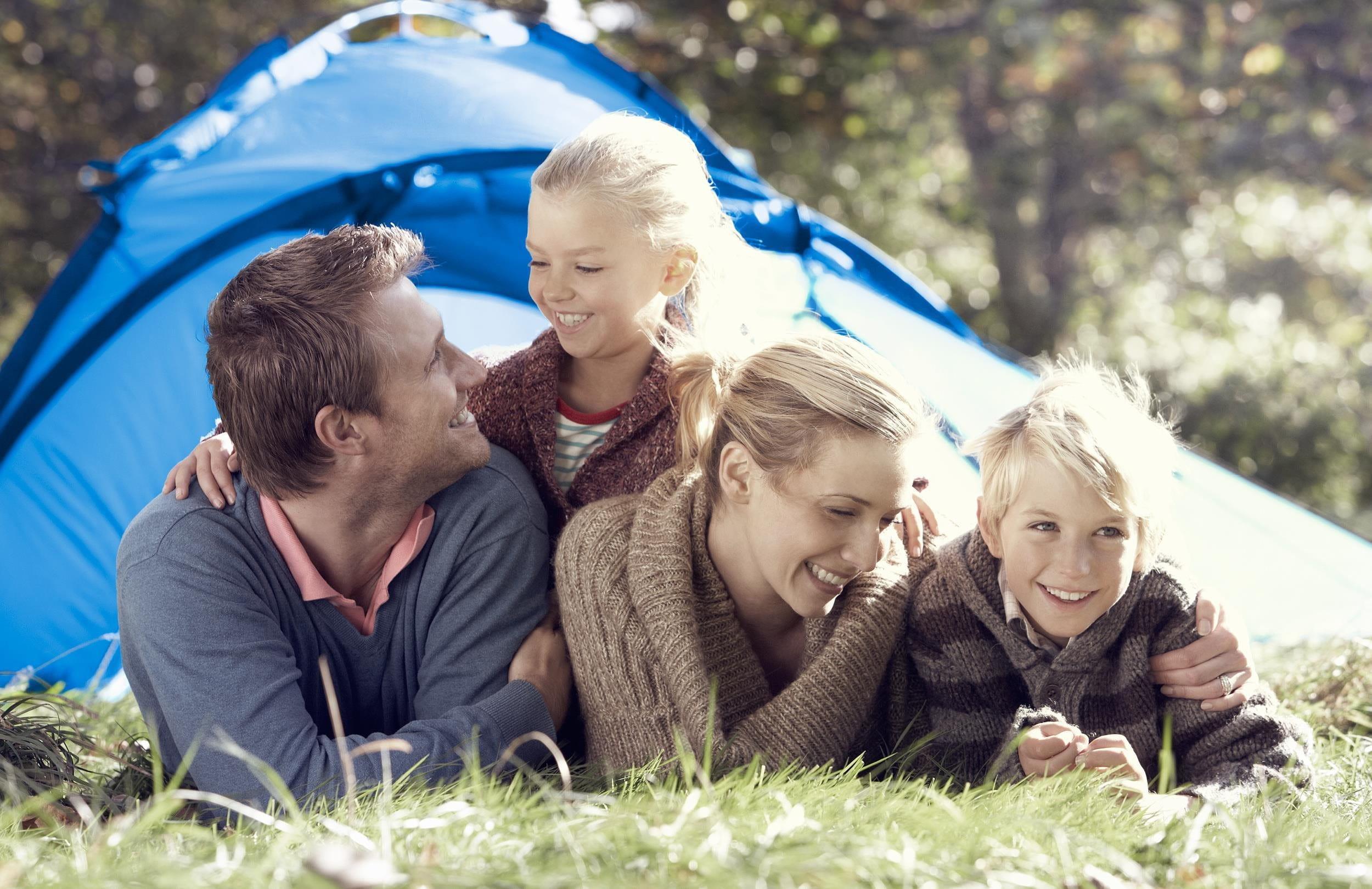 Famile liegt vor einem Zelt
