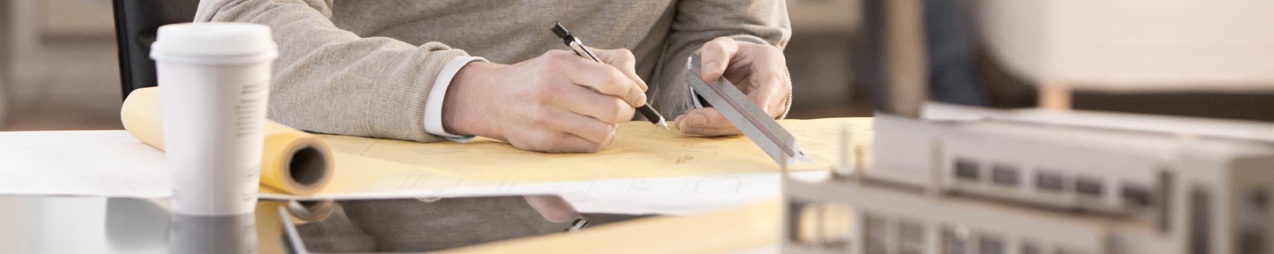 Ein Mann zeichnet Skizze am Arbeitsplatz.