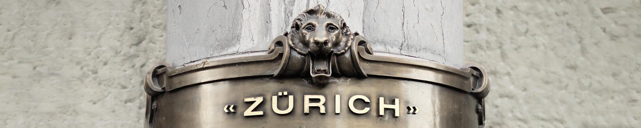 Eine Säule mit dem alten Logo von Zurich.