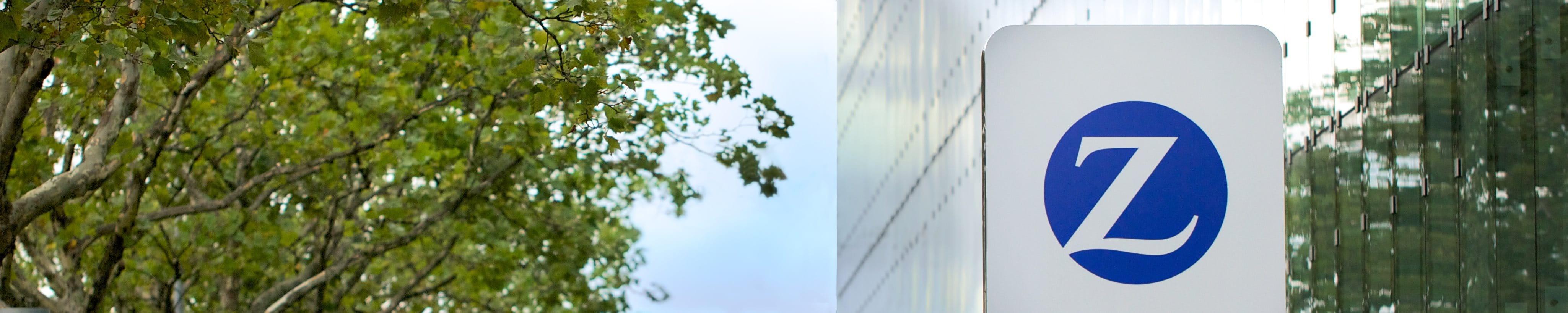 Un cartello della Zurich con degli alberi.
