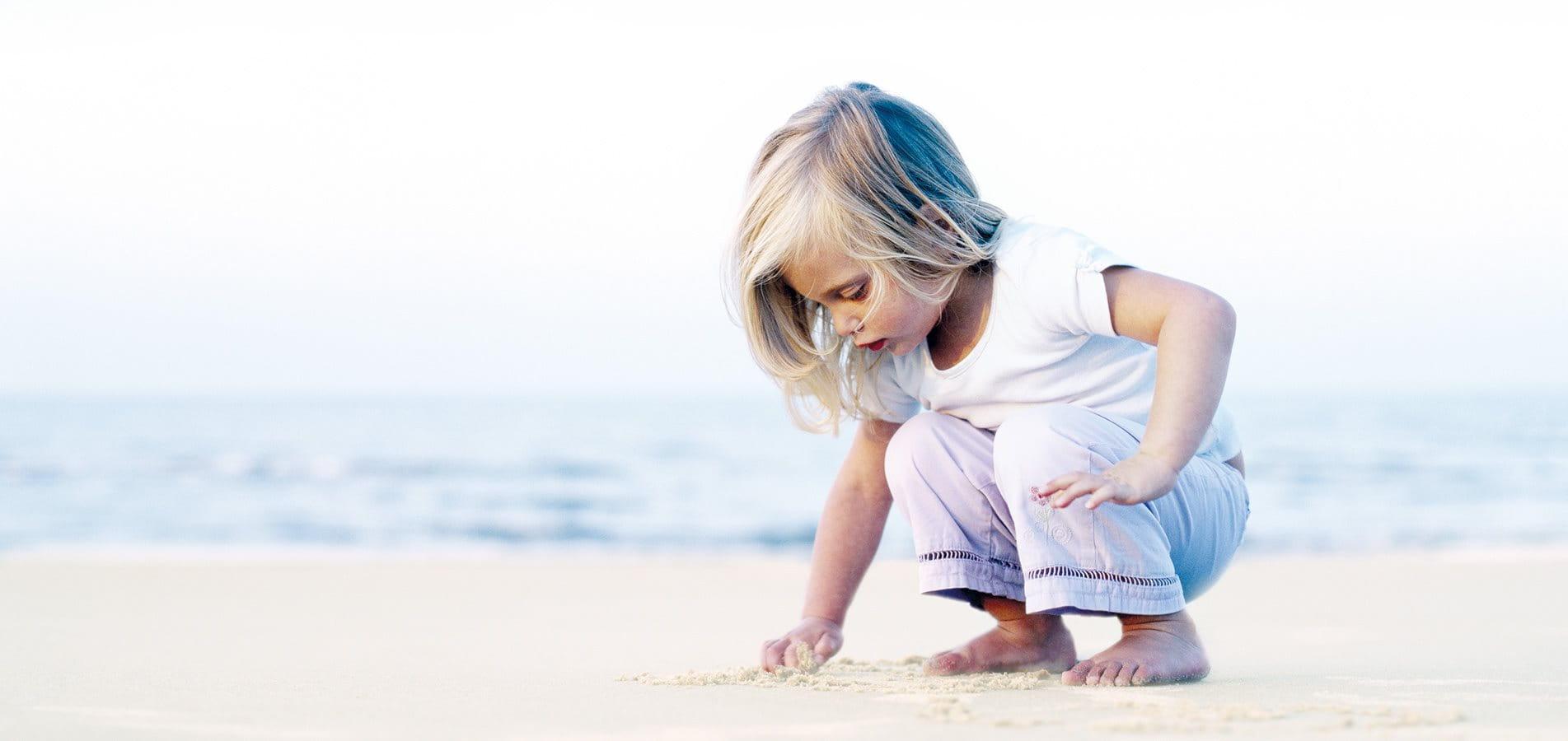 Ein kleines Mädchen spielt am Strand